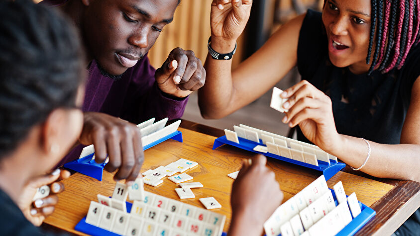 A group of adult friends playing the board game Rummikub
