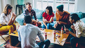 Friends playing a board game together around a table