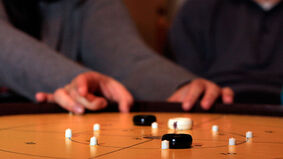 A player takes a shot in dexterity game crokinole