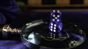 Two six-sided dice on a magnifying glass