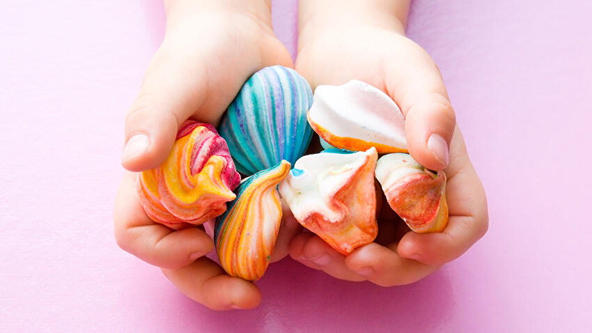 Colourful meringues in hands