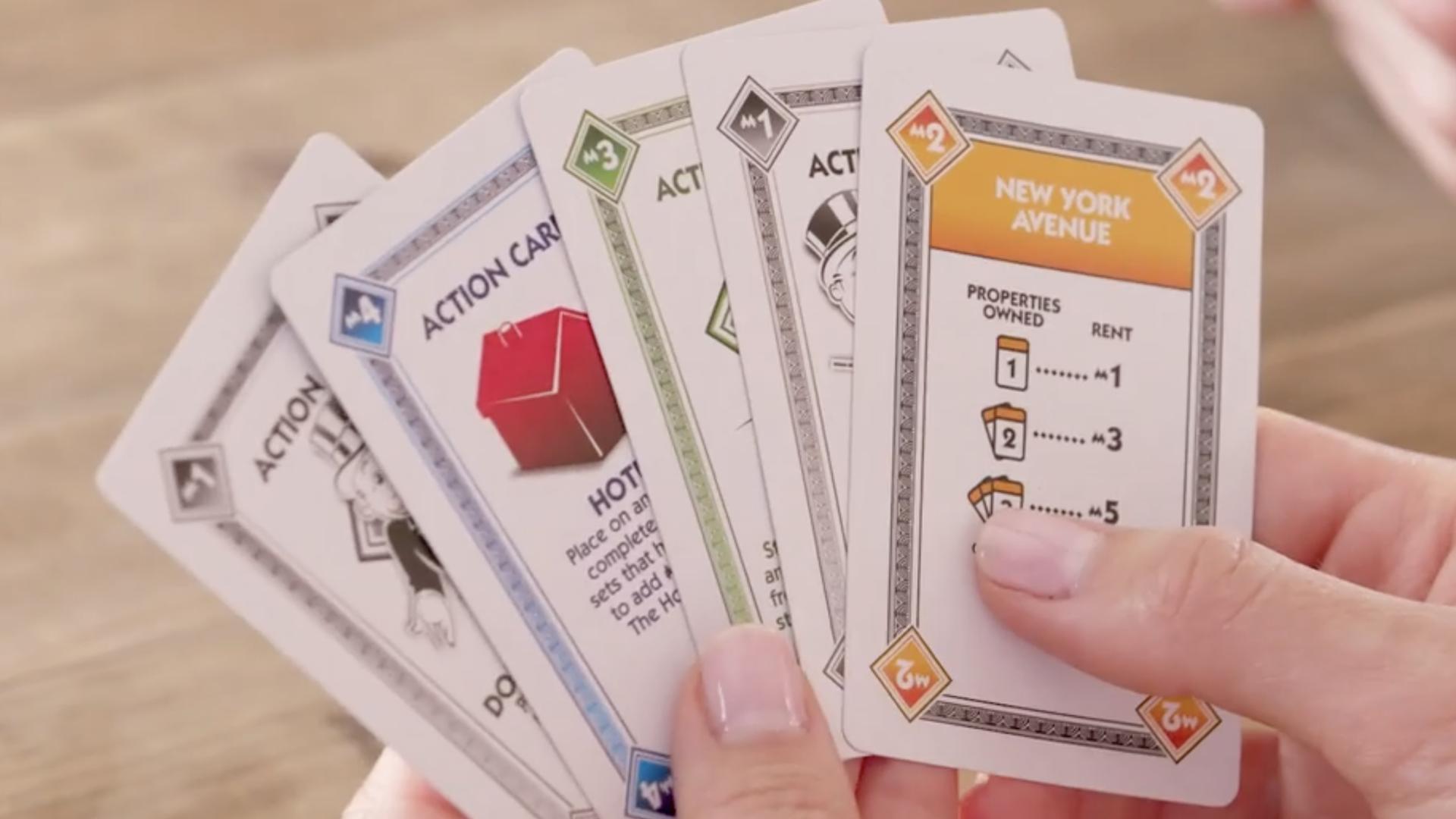 Monopoly Deal cards held in hands