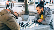 Two people playing chess in a park